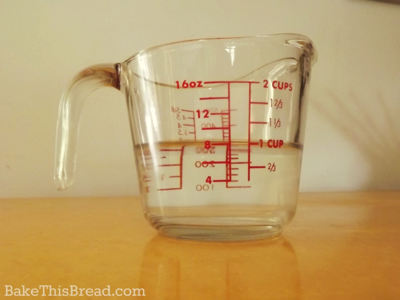 Glass Measuring Cup with 1 cup warm water for homemade yeast bread by bake this bread