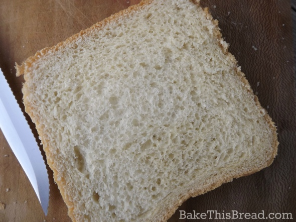 Slice of homemade yeast wheat bread using bread machine on wooden cutting board by bake this bread