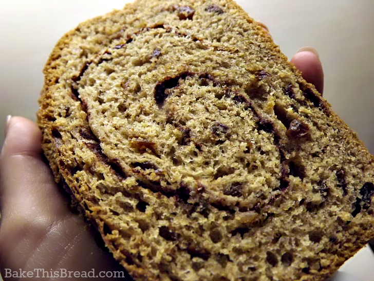 Holding a hot slice of homemade cinnamon swirl bread by bake this bread